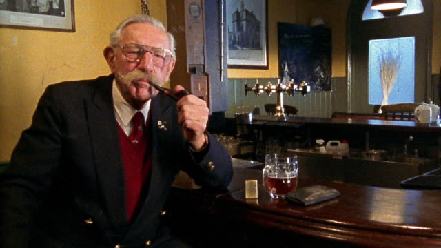 Medium shot senior man smoking pipe at bar in pub with glass of beer next to him