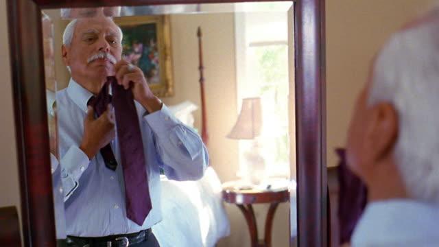 Medium shot senior man tying tie in front of mirror with senior woman coming to help him