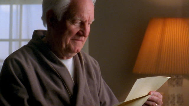 Medium shot senior man wearing robe reading letter / putting letter in envelope