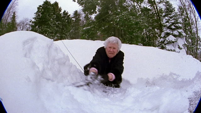 Medium shot senior woman scraping snow off of car