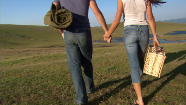 Medium shot shadow of couple walking/ pan couple in jeans walking on grass, holding hands, and carrying picnic basket and blanket/ couple walking off camera/ close up grass/ Umbria