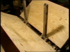 Medium shot sheets of plywood rotated through machine on assembly line
