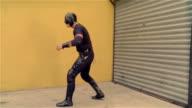 Medium shot side view luchador 'Shadow' flexing muscles in front of garage door/ Monterrey, Mexico