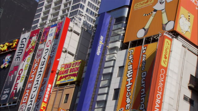 Medium shot signs on exteriors of electronics stores in Akihabara district / Tokyo
