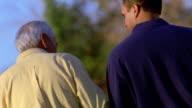 Medium shot slow motion senior man and younger man walking + talking outdoors / Arizona