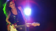 Medium shot slow motion young woman playing an electric guitar, singing, dancing about