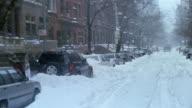 2003 medium shot snow falling on Upper West Side street during blizzard / man shoveling snow / New York City