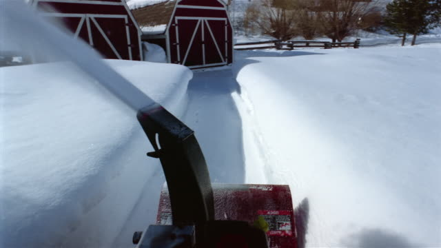 Medium shot snowblower point of view clearing path towards barn