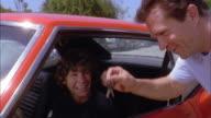 Medium shot son sitting in car driver's seat / father handing him car keys through window