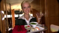 Medium shot Stewardess carrying tray of sushi in private airplane