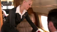 Medium shot Stewardess serving tray of sushi to businessman in private airplane