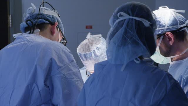 Medium shot, surgeons perform procedure in hospital operating room