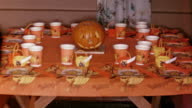 1958 medium shot table set for Halloween party with jack o' lantern in center