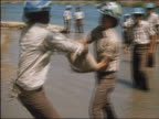 1986 medium shot tanuniformed brigade passing sandbags ankledeep in flood water