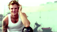Medium shot tattooed man in white tank top posing and holding motorcycle helmet with motor scooter in background