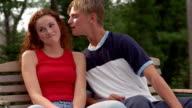 Medium shot teen boy leaning over and kissing teen girl on cheek on outdoor park bench
