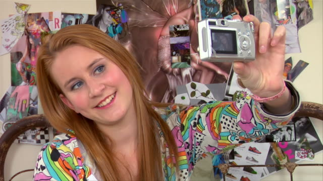 Medium shot Teen girl taking self portrait with digital camera in bedroom / Brooklyn, New York, USA