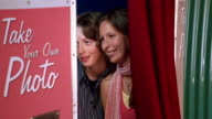 Medium shot teenage boy and girl posing in photo booth
