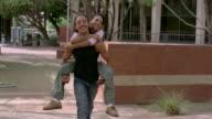 Medium shot teenage boy carrying teen girl on his back