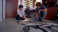 Medium shot teenage boys playing w/electric slot cars on racetrack