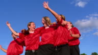 Medium shot teenage girls soccer team celebrating and hugging / Vermont