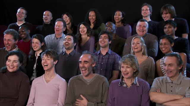 Medium shot theater audience laughing/ England
