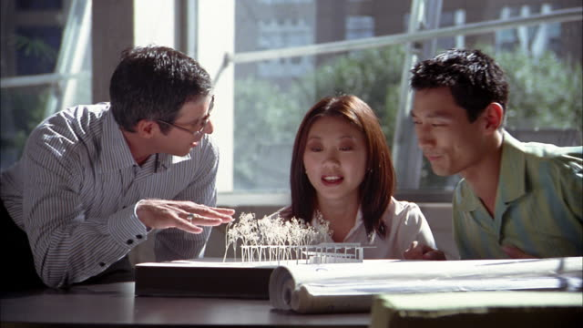Medium shot three people looking at architecture building model and reviewing blue prints