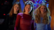 Medium shot three teen girls walking toward camera with lights flashing in background