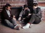 1955 medium shot three teenage boys sitting on sidewalk smoking cigarettes and playing cards