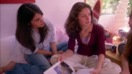 Medium shot three teenage girls sitting and talking in bedroom