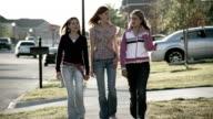Medium shot three teenage girls walking down suburban street / talking and smiling