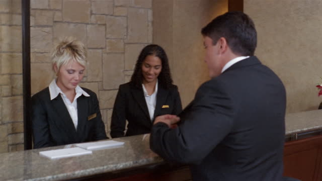 Medium shot three women at hotel reception desk / woman helping businessman check in