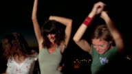 Medium shot three women dancing outdoors w/men in the background