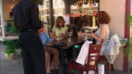 Medium shot three women sitting at outdoor cafe with waiter standing by/ woman giving camera to waiter/ pan waiter taking photo of three women at table/ Westfield, New Jersey