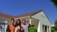 Medium shot tilt down family waving next to real estate sign with house in background / California