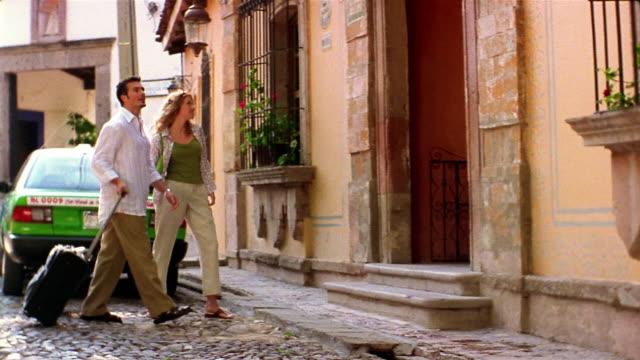 Medium shot tilt up cobblestone street /  couple entering hotel with luggage