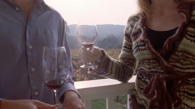 Medium shot tilt up couple walking on porch at vineyard, holding wine and kissing/ couple kissing/ Napa Valley, California