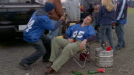 Medium shot tilt up drunk man asleep in chair at tailgate party as people stand behind him/ Connecticut