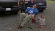 Medium shot tilt up drunk man asleep in chair/ two women coming up behind him and putting mascot bear head on him/ Connecticut