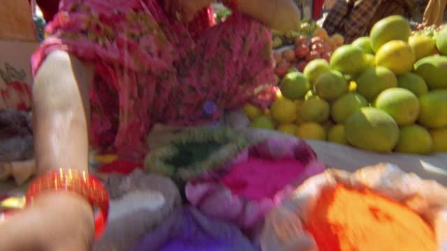 Medium shot tilt up from colorful powders (dyes) to female Nepalese street vendor / Kathmandu, Nepal
