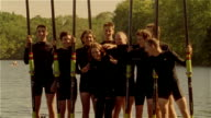 Medium shot tilt up from water to portrait of crew team standing on pier holding oars / posing with coxswain / tousling her hair