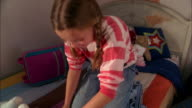 Medium shot tilt up girl sitting on knees on top of packed suitcase and zipping suitcase closed