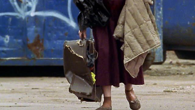 Medium shot tilt up homeless senior woman walking across street with damaged suitcase