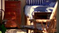Medium shot tilt up pan interior of bedroom with bed, dresser and open windows / Provence, France
