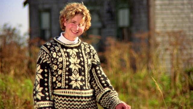 Medium shot tilt up portrait blonde teen girl in sweater standing in grass smiling / house background / Nova Scotia