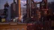 Medium shot tilt up smokestacks at steel mill