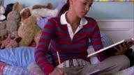 Medium shot tilt up teenage girl sitting on bed / reading and doing homework