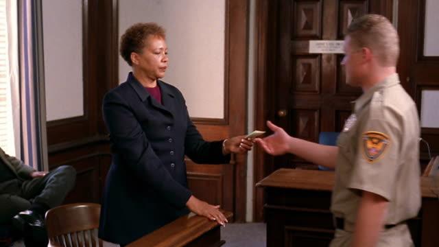 Medium shot tilt up tilt down jury forewoman handing bailiff verdict on small slip of paper