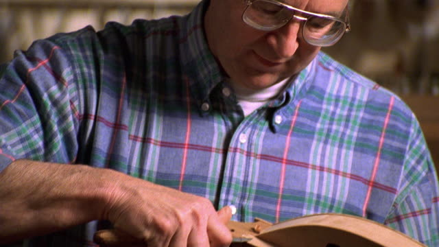 Medium shot tilt up tilt down man shaping musical instrument (dulcimer) with sharp tool