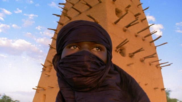 Medium shot tilt up Tuareg tribesman wearing shesh headdress standing in front of Agadez Mosque / Niger